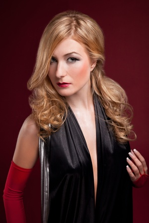 Perfect blonde in a black dress on red photo