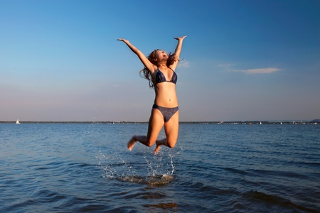 young woman on the sky and water background photo