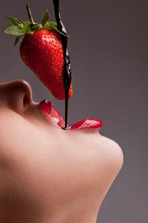 labios sexy: niña comiendo fresas con chocolate sauc