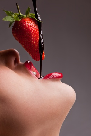 labios sensuales: ni�a comiendo fresas con chocolate sauc