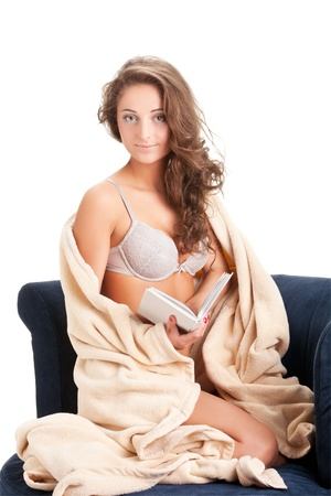 young woman sitting on chair covered with blanket photo