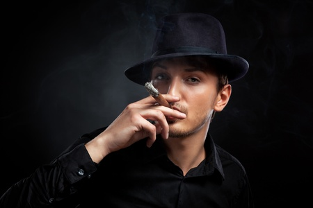 Gangster look. Man with hat and cigar.