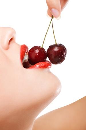 labios sexy: boca de la joven mujer con cerezas rojas Foto de archivo