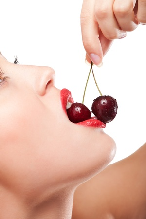 young womans mouth with red cherries photo