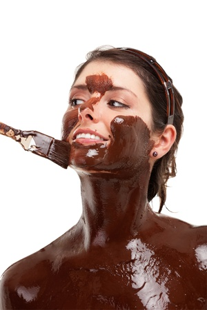 young woman having a chocolate face mask photo