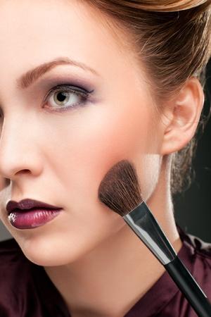 Beautiful woman with makeup brush photo