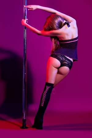 attractive sexy woman pole dancer performing on stage photo