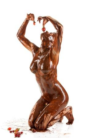 裸のブロンドの女性は甘いクリームチョコレートを覆った