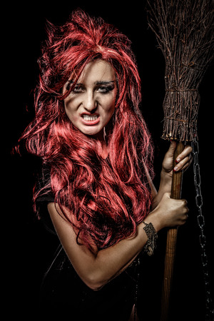 redhaired: Evil red-haired witch and her broomstick Stock Photo