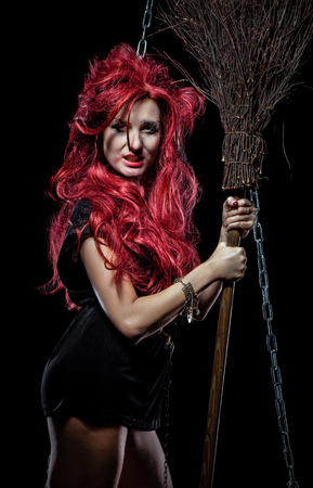 Evil red-haired witch and her broomstick photo