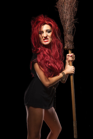 beldam: Evil red-haired witch and her broomstick Stock Photo