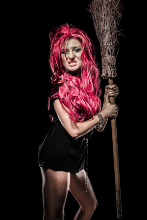 Evil red-haired witch and her broomstick Stock Photo