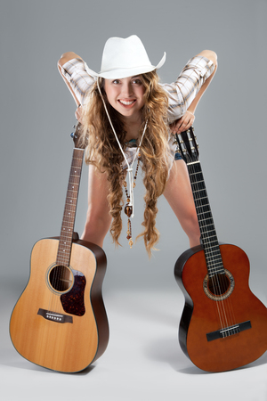 Sesy cowgirl in cowboy hat with a nylon string acoustic guitar