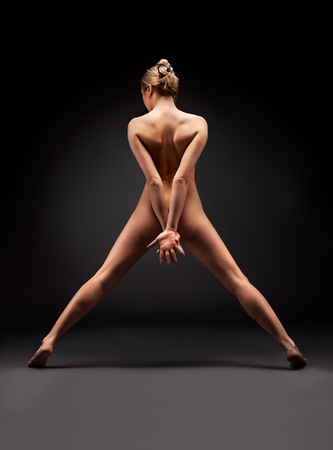 Naked woman is standing back on a black background, low-key photos. photo