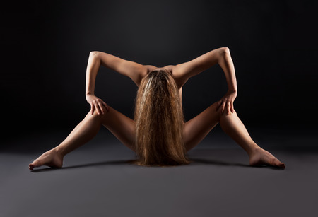 Naked woman is sitting on a black background, low-key photos. photo