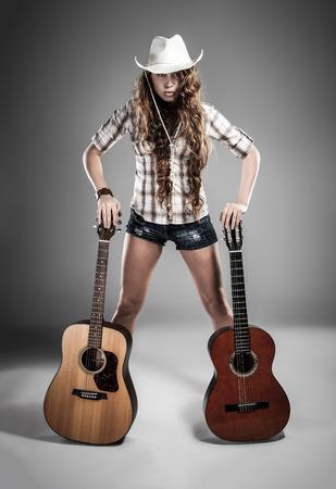 rocker girl: chica de moda con la guitarra tocando hard-rock. Imagen con efecto de alto contraste. Foto de archivo