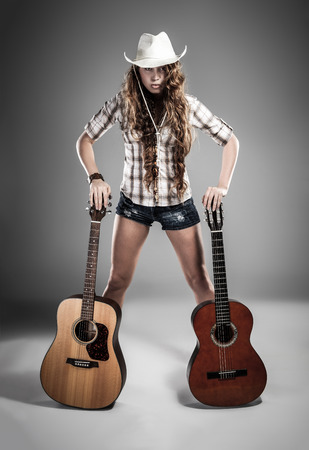 hardrock: Fashion girl with guitar playing hard-rock. Picture with high contrast effect.