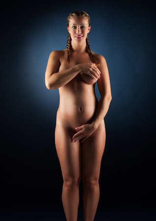 Beautyful Naked Pregnant woman caressing her belly. 32 week Stock Photo