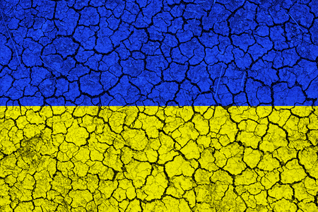 famine: Flag of Ukraine painted on cracked wall. Political concept. Old texture. Vintage design. Ukraine flag on cracked earth. Famine and drought. Natural disaster. Stock Photo