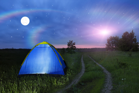 invaders: Alien spaceship - UFO over the field at night. Camping tent glows under a night sky full of stars. Outdoor Camping adventure. Travel concept. Extraterrestrial life. Invaders from another planet.