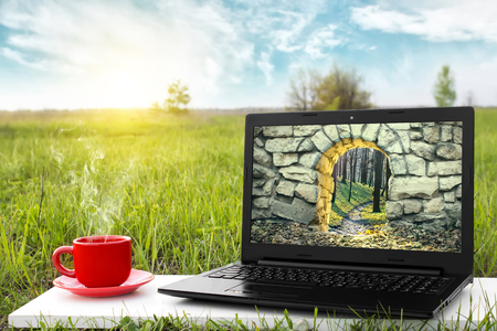 otherworldly: Mysterious entrance to new life or beginning. Step to new opportunities. The entrance to another world. Journey to fairytale. Laptop and a cup of hot coffee outdoors. Travel concept. Beautiful nature.