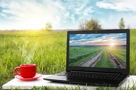 Laptop and cup of hot coffee on the background picturesque nature, outdoor office. Travel concept. Business ideas. The rest of nature. Agriculture and agribusiness.