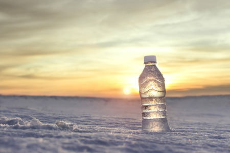 thirst quenching: Bottle of cold water in the snow at sunset. Advertising by mineral water. Quenching thirst. Fresh frosty morning. Close-up view on the background of beautiful nature. Stock Photo