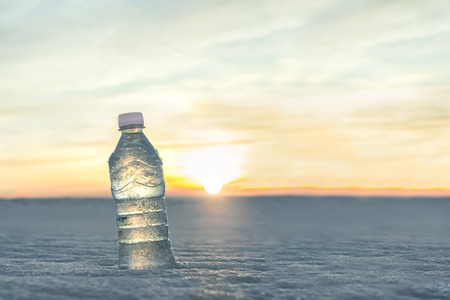 quenching: Bottle of cold water in the snow at sunset. Advertising by mineral water. Quenching thirst. Fresh frosty morning. Close-up view on the background of beautiful nature. Stock Photo