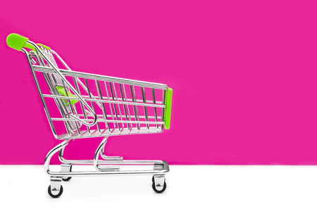 grocery trade: Cart from the grocery store on a pink background. Retail trade and advertising. Purchase in the store.