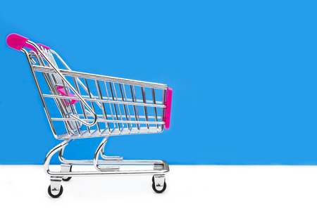 grocery trade: Cart from the grocery store on a blue background. Retail trade and advertising. Purchase in the store.
