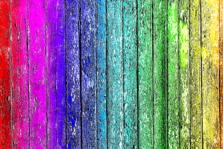 Old shabby wooden planks with cracked color paint, background old panels. Color-Peel wood texture. Multicolored fence.