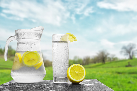 quenching: Fresh cold water with lemon and ice in a pitcher on the table.Homemade lemonade with fresh citruses on the background of nature. Quenching thirst.The condensation on the jug and a glass of cold water. Stock Photo