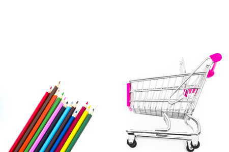 school notebook: Back to school concept with shopping cart and multicolored pencils on the white background. Notebook in a cage. The first of September. The day of knowledge. Buying school supplies. Stock Photo