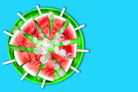 Slice of watermelon with ice cubes on a blue background. Ice cream with the taste of watermelon. Sweet dessert. The summer mood. Stock Photo