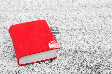 The winters tale. The book on the table, covered with snow. Winter mood. Hello winter. The concept of Christmas and New Year. Magic composition. Stock Photo