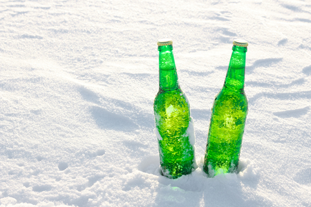 Two bottles of cold beer on the snow at sunset. Close up view.