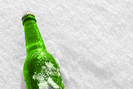 Bottle of cold beer on the snow. Close up view.