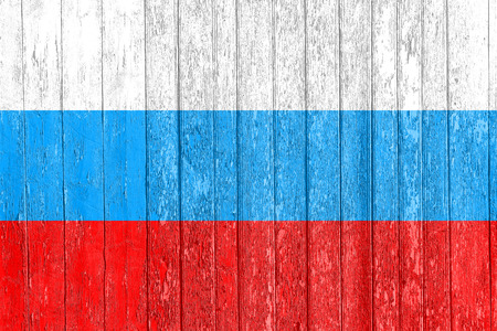 The Russian flag painted on a wooden fence. Political concept. Old texture. Vintage design. Closeup view.