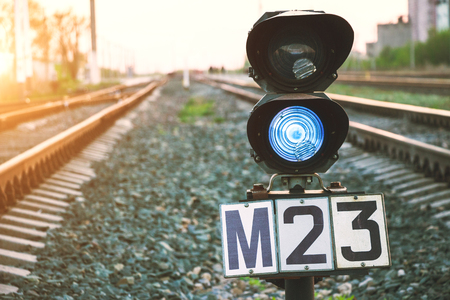 Traffic light shows blue signal on railway. Prohibiting signal. Railway station. Regulation and control of movement. Travel by train. Rail transportation.