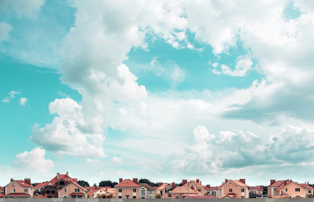 Row of new townhouses on the background of blue sky.