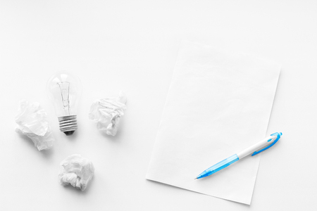 poems: New business idea and innovation in trade. The concept of selling and buying. Pen, blank sheet and crumpled sheets of paper on the wooden white background. Writing poetry. Never give up. Stock Photo