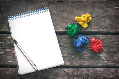 poems: Notepad with blank sheet of paper, pen and multicolored crumpled sheets of paper on the old wooden background. Workplace of the artist, writer. Never give up. Stock Photo