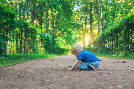 Little boy sitting on the ground and playing in the park. Beautiful nature background at sunset. Summer mood.
