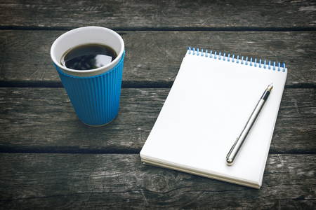 poems: Cup of hot coffee, pen and notepad, blank sheet of paper on the old wooden background. Business plan. Writing poetry.