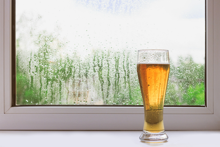 Glass of cold beer on the windowsill on a rainy summer day. The view from the window. Rain drops on glass. Holiday and vacation. Stock Photo