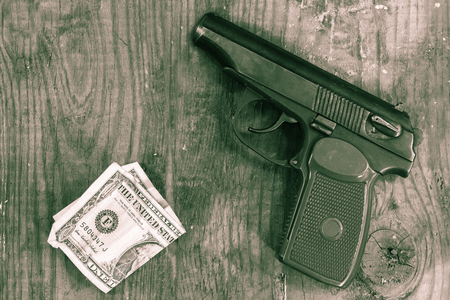 The gun and money on wooden table. Concepts: crime, contract killing, killer, robbery, extortion, money laundering.