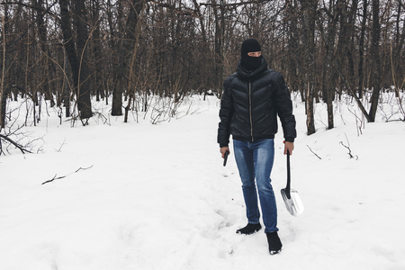 Murderer in the black mask with gun and shovel leaves place of the crime, going through the snow in the dark forest at the evening. Stock Photo