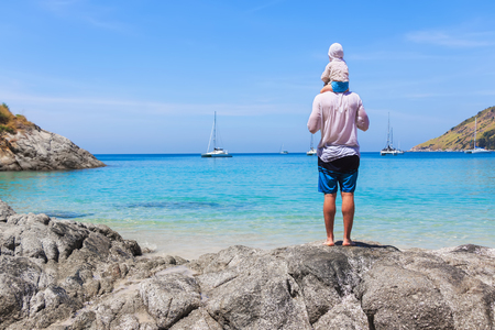 Father and son on the shore of the azure sea watching for drifting yachts. Lifestyle, vacation, happiness, joy concept. Leisure activities.
