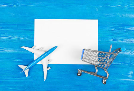 Model of airplane, grocery cart and blank sheet of paper on the blue wooden background. Travel concept. Ticket purchase.