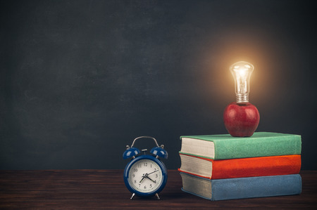 Stack of multicolored textbooks on a wooden table, apple with light bulb and alarm clock. Back to school.